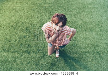 High Angle View Of Beautiful Happy Girl Smiling At Camera While Standing On Green Grass