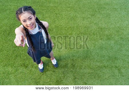 Beautiful Smiling Asian Girl Pointing At Camera With Finger While Standing On Green Grass