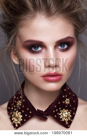 Close up portrait of beautiful young model with unusual makeup, perfect skin, volume hairstyle. Trendy smoky eyes and kissed lips.