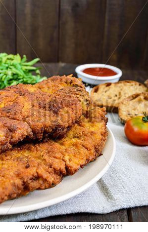 A large Viennese schnitzel on a dark wooden background. Vertical view