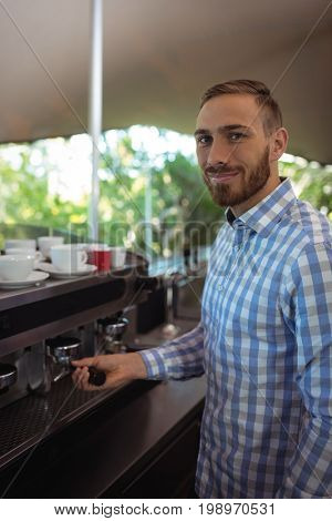 Waiter using tamper to press ground coffee into a portafilter in restaurant