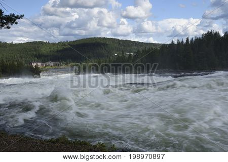 The rapid (Storforsen) in the river (Piteälven) with the hotel in background picture from the North of Sweden.
