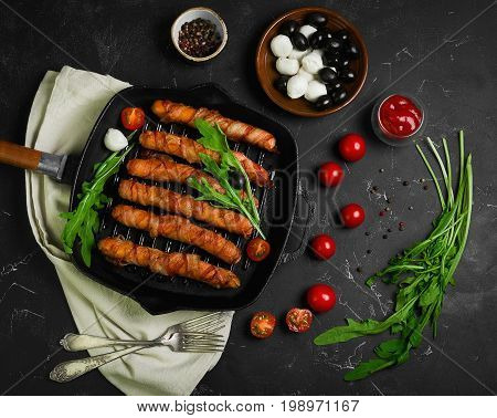 Preparation of roast grill sausages wrapped spirally in bacon on a cast-iron frying pan. Ingredients for sausages in bacon cherry tomatoes, rucola salad, pepper. Black concrete background.