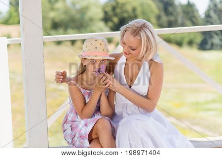 Mother with her liitle girl, daughter sniffing a flower. Summer time young woman on a walk with her child.