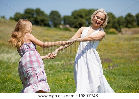 Mother and daughter dancing in a meadow. Happy family, mom and small daughter spending time outdoors.