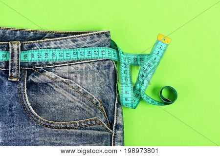 Blue Jeans With Measure Tape Isolated On Green Background