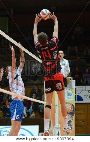 KAPOSVAR, HUNGARY - MARCH 6: Krisztian Csoma (14) posts the ball at a Hungarian National Championship volleyball game Kaposvar vs. Kazincbarcika, March 6, 2011 in Kaposvar, Hungary.