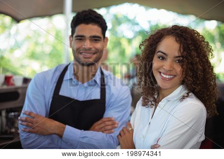 Portrait of smiling waiter and waitress standing with arms crossed at counter in restaurant