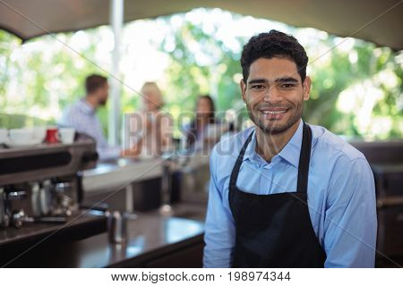 Portrait of smiling waiter at counter in restaurant