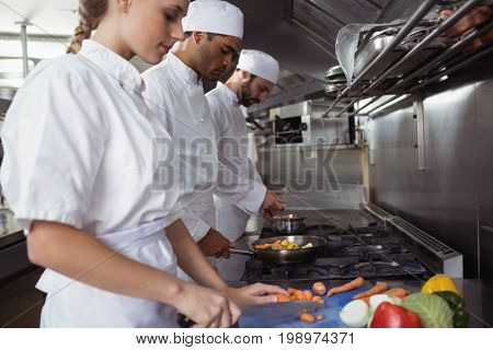 Chefs chopping vegetables on chopping board in the commercial kitchen