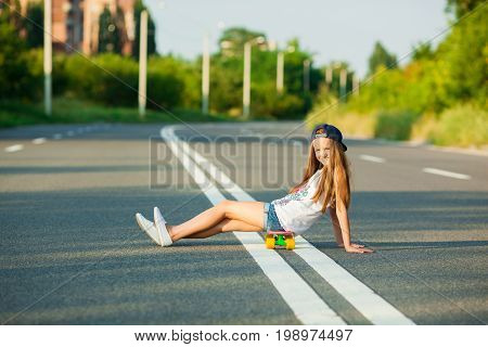 A young girl with penny board outside the city at the road. poster