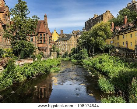 Tranquil Edinburgh summer scene of Water of Leith flowing through picturesque and historic Dean Village