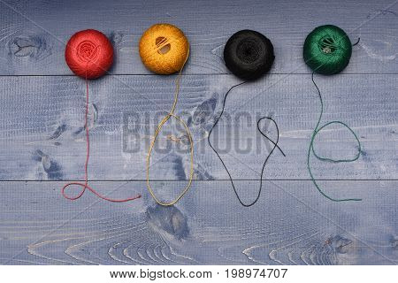 Balls Of Yarn With Their Threads Shaped As Love Word