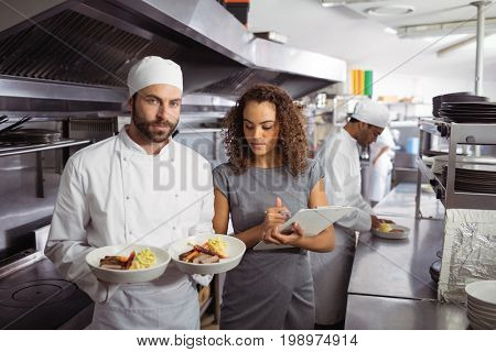 Portrait of chef presenting his food plates in the commercial kitchen