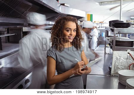 Portrait of manager writing on clipboard in commercial restaurant