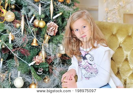 Happy kid girl 7-8 year old laughing in room over christmas tree.