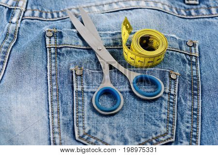 Things for making clothes on back pockets of jeans close up. Tailors tools with denim fabric selective focus. Metal scissors and yellow measure tape on denim pants. Tailoring and design concept.