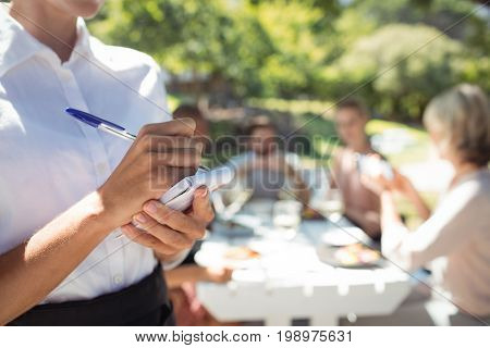 Mid section of waitress writing order on notepad in restaurant
