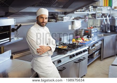 Portrait of smiling chef standing with arms crossed in commercial kitchen at restaurant