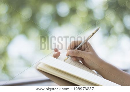 Hand writing of women on note paper on balcony and green bokeh of tree background in morning