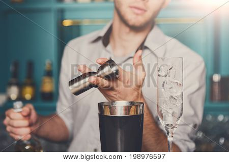 Unrecognizable bartender in bar interior pouring syrup into measuring glass for making cocktail. Service industry occupation.