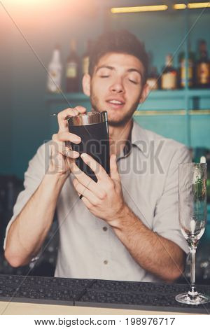 Young professional bartender in bar interior shaking and mixing alcohol cocktail with shaker in hands