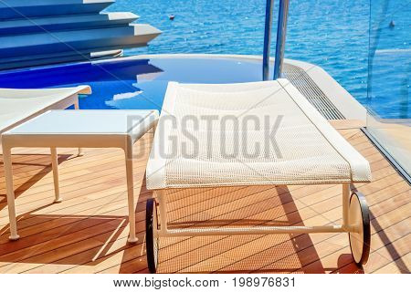 Chaise-longue and table on the wooden deck near the pool on a background of the sea close-up