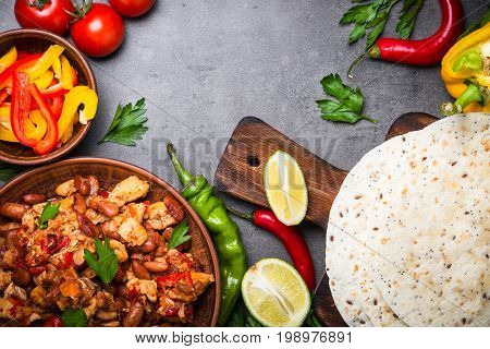 Cooking Mexican taco with meat beans and vegetables at black slate table. Latin american food background. Top view.