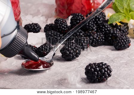 Juicy blackberries with leaves of fresh green mint, jam in a bottle and a tea spoon full of jam on a white table-cloth., close-up. Summer fruits on a white background.
