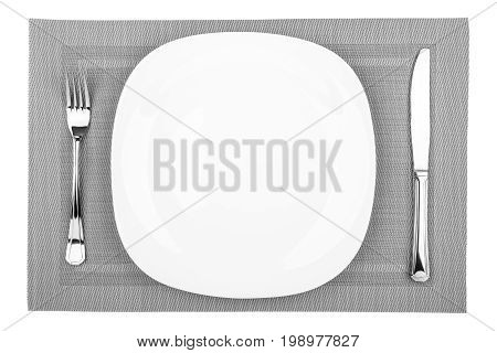 Fork table knife and empty white plate on a placemat closeup top view