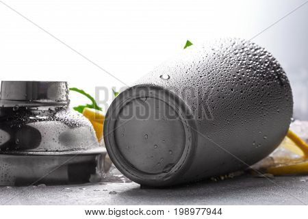 Silver metallic moist shaker isolated on a blurred white background, fresh mint and juicy lemon on a white table-cloth, yellow sliced lemon, green leaves of mint, drops of water on a metallic shaker.
