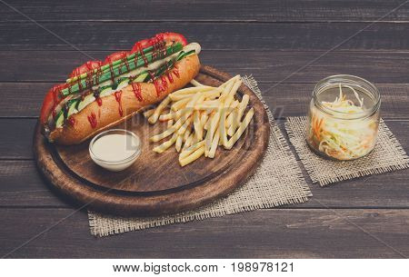 Hot dog and french fries. American fast food restaurant cuisine on wooden platter on table.