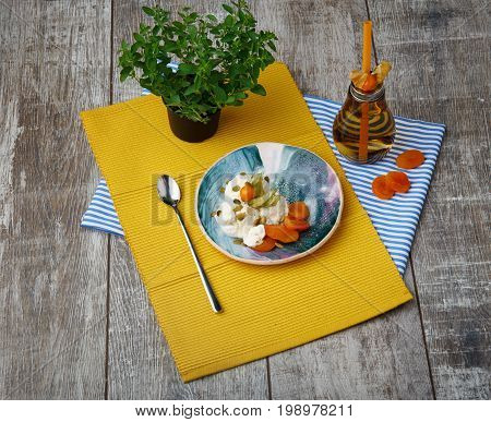 Top view of white sweet ice-cream with dried orange apricots, fresh juicy physalis, pumpkin seeds, shining metallic tea spoon, little green tree, yellow and striped napkins, bottle with a beverage on a wooden background.