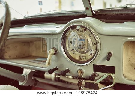 Evora Portugal - June 2 2017: Old cabin console speed meter and steering wheel in a vintage retro car Morris Minor. Retro toning vintage style image.