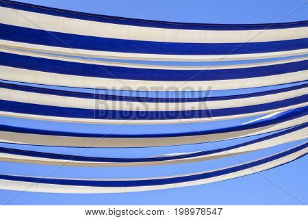 Abstract effect of the blue and white striped canvas of a restaurant awning in the sunshine against clear blue sky background