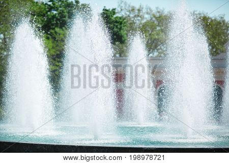 Closeup of fountain with fresh cool water, splashes of water on a natural background, summer nature, refreshing moisture, green trees, blue water, drops.