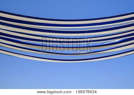 Abstract effect of the blue and white striped fabric of a restaurant canopy in the sunshine against clear blue sky background with copy space