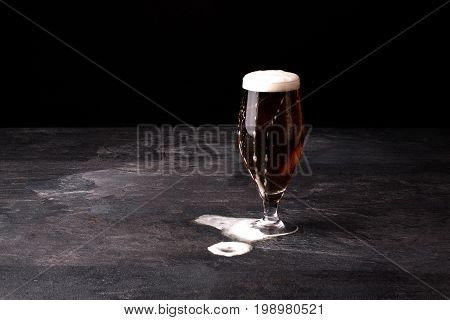 A huge glass of beer filled up with brown ale and with white light foam blowed away on a stone table on a dark background, copy space. Alcohol beverage.