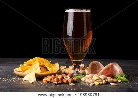 A moist glass of brown ale, with crunchy crisps, sappy tender slices of bacon, handfuls of peanuts, hazelnuts, and pistachios on a dark background. Copy space. Snacks for beer.