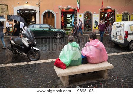 ROME ITALY - OCTOBER 18 2016: Two unknown tourists with colorful rain coats sitting on a bench