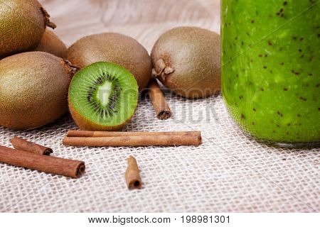Macro picture of brown kiwi fruits with aromatic cinnamon on a cream fabric background. A cold kiwi milkshake in a glass jar next to natural green fruits. Vegetarian ingredients. Copy space.
