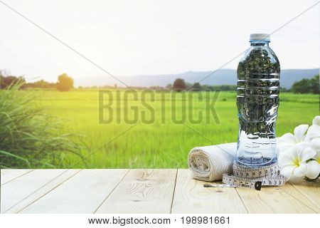 bottle of water on a wooden table with white flower and handkerchief on nature background.