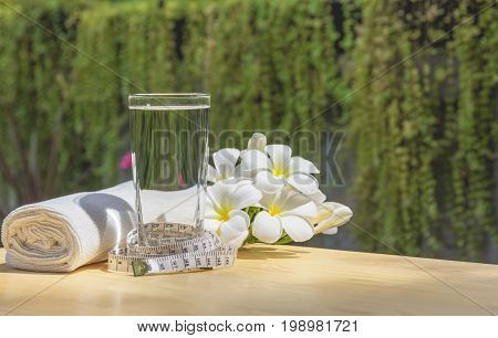 glass of water on a wooden table with white flower and handkerchief on nature background.