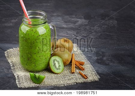 A close-up picture of a mason jar full of kiwi yogurt and natural ingredients on a gray background. Cool smoothie next to a group of exotic kiwis on a cream fabric. Summer beverage. Copy space.