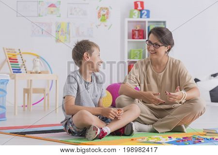 Boy And Therapist Sitting On Floor