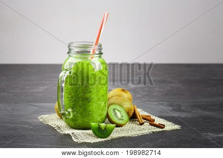 A close-up of a mason jar of kiwi yogurt and natural ingredients on a fabric on a gray background. Green beverage and fragrant cinnamon next to a group of exotic kiwis. Copy space.