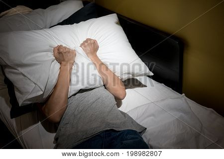 Depressed Woman Covering Her Face With White Pillow And Screaming