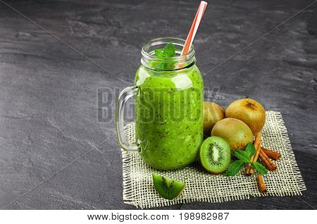 Close-up of a green kiwi beverage on a gray stone background. A cocktail in a mason jar with a colorful straw. Colorful kiwis, cinnamon sticks and mint leaves next to a cool drink. Copy space.