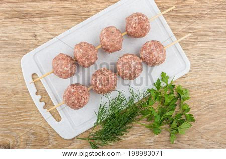 Strung On Skewer Meatballs On Cutting Board And Greens