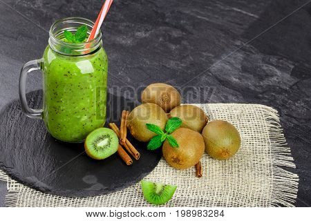 A composition of tropical kiwis, mason jar full of kiwi juice, fresh mint and cinnamon sticks on a black tray on a dark table background. Healthy ingredients for summer beverages. Copy space.